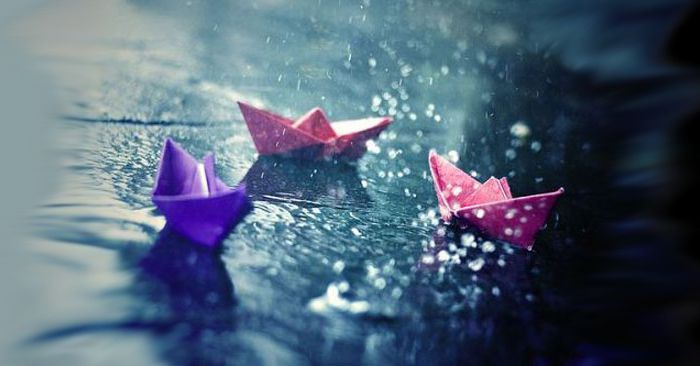 paper boats in rain raindrops splattering